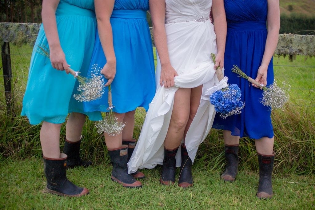 A bride and her bridesmaids lift the hems of their dresses to reveal that they are wearing gumboots underneath