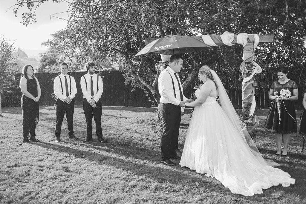 A bride and groom say their vows under an apple tree while someone holds an umbrellaa over them and their bridal party looks on in the rain.