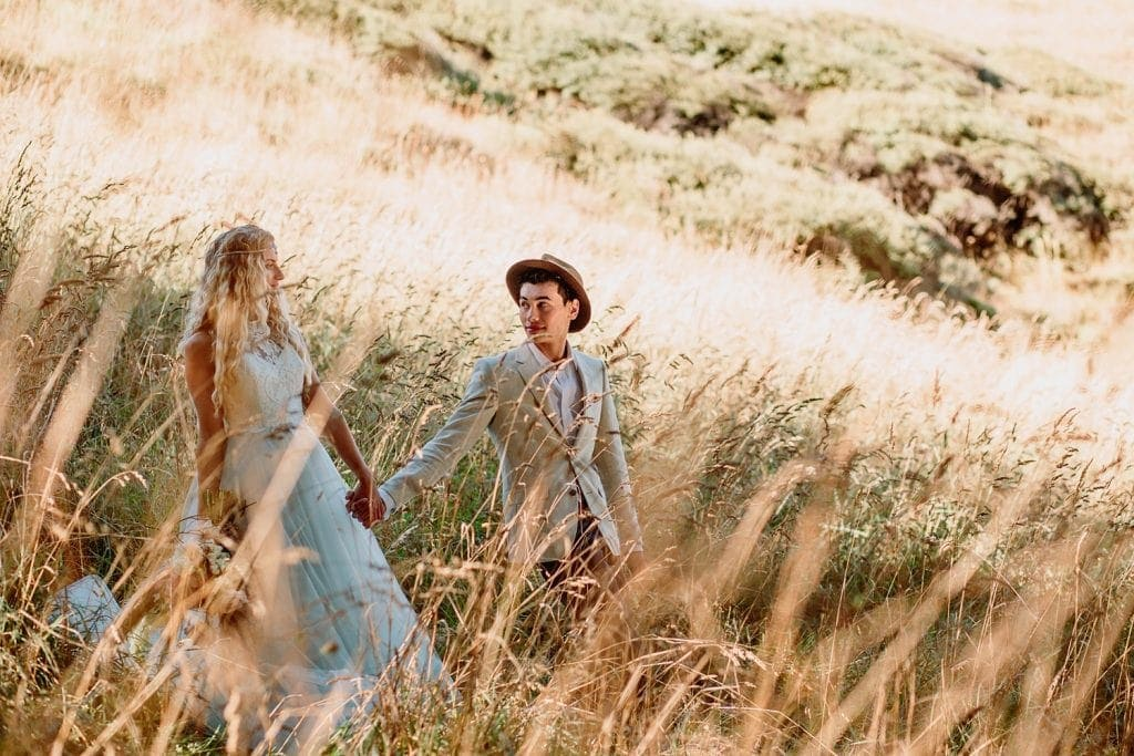 A bride and groom holding hands and walking through a tall grassy field in the summer